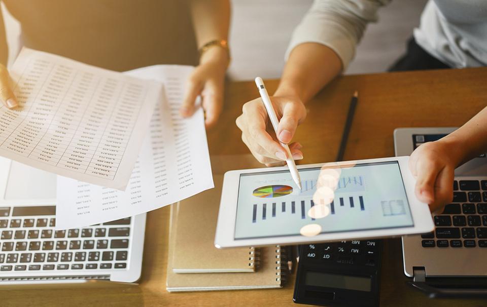 Un miembro de una empresa muestra a otro la importancia de Business Intelligence en la estrategia de la compañía